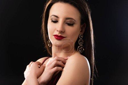 Photo pour Femme attrayante avec des boucles d'oreilles regardant vers le bas sur fond noir - image libre de droit