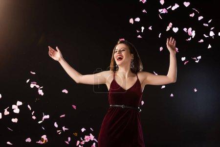 Photo pour Femme souriante en robe debout près de confettis tombant sur fond noir - image libre de droit