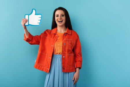 smiling woman in jacket holding paper like on blue background