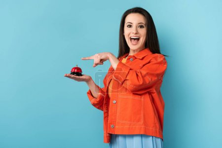 shocked woman pointing with finger at service bell on blue background