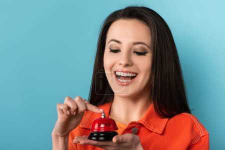 smiling woman ringing in service bell on on blue background