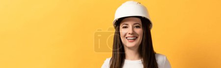 panoramic shot of smiling handywoman looking at camera isolated on yellow