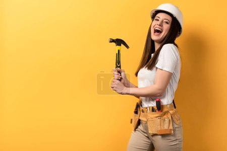 Photo for Smiling handywoman in helmet holding hammer on yellow background - Royalty Free Image