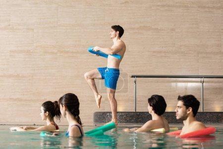 Photo pour Vue latérale de l'entraîneur avec la nouille de la piscine en train de travailler avec un groupe de personnes pendant la danse aérobique aquatique dans la piscine - image libre de droit