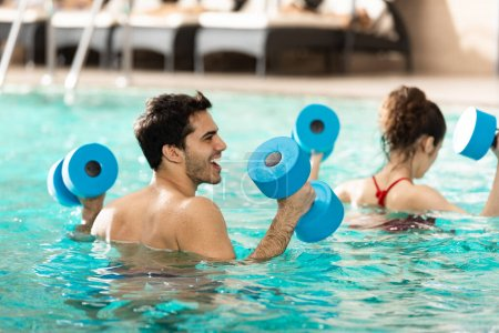 Photo pour Selective focus of cheerful man with dumbbells during water aerobics in swimming pool - image libre de droit