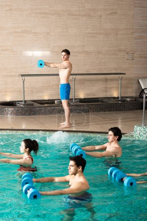 Photo pour Side view of trainer holding dumbbells while exercising with group of young people in swimming pool - image libre de droit