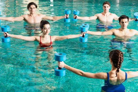 Photo for Trainer holding barbells while exercising with group of young people in swimming pool - Royalty Free Image