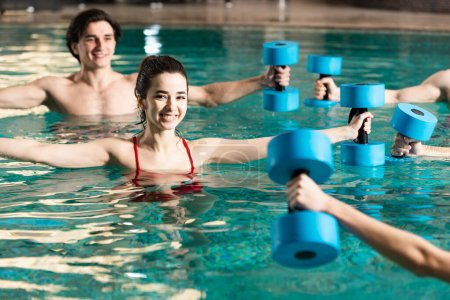 Photo for Selective focus of smiling young people exercising with barbells during water aerobics in swimming pool - Royalty Free Image