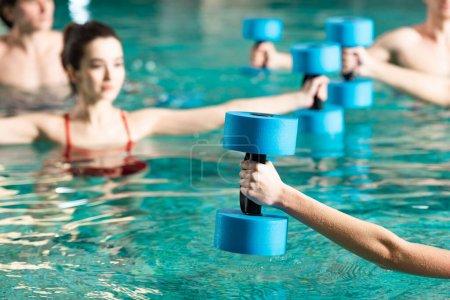 Enfoque selectivo del entrenador con barra de pesas trabajando con personas en la piscina