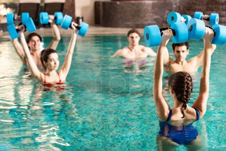 Selective focus of trainer holding barbells while exercising water aerobics with people in swimming pool