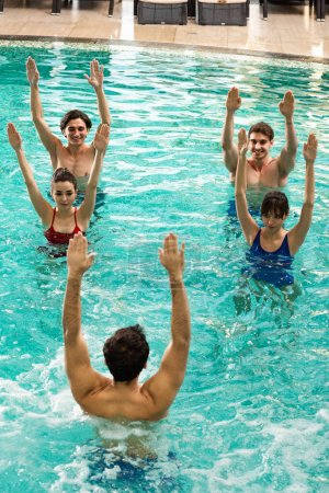 Photo for Overhead view of trainer working out with group of young people during water aerobics in swimming pool - Royalty Free Image