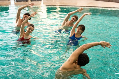 Photo for Trainer working out with smiling people during water aerobics in swimming pool - Royalty Free Image