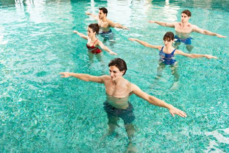 Foto de High angle view of trainer working out with young people during water aerobics in swimming pool - Imagen libre de derechos