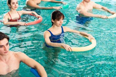 Photo pour Vue en angle élevé des jeunes s'entraînant avec des nouilles de piscine dans la piscine - image libre de droit