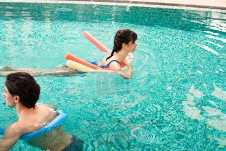 Photo pour Vue latérale de l'homme et de la femme nageant dans la piscine avec nouilles de piscine - image libre de droit