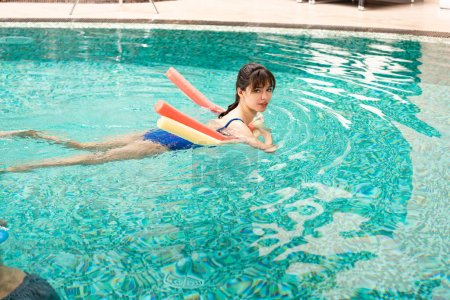 Photo for Side view of young woman looking at camera while swimming with pool noodles in swimming pool - Royalty Free Image