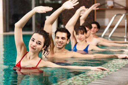 Selective focus of smiling trainer looking at camera near people exercising in swimming pool