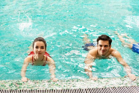 Photo for Smiling man and woman training together in swimming pool - Royalty Free Image