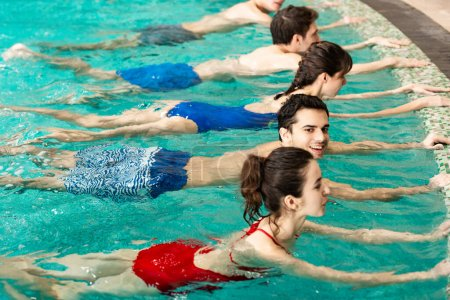 Photo for Side view of smiling young people exercising water aerobics in swimming pool - Royalty Free Image