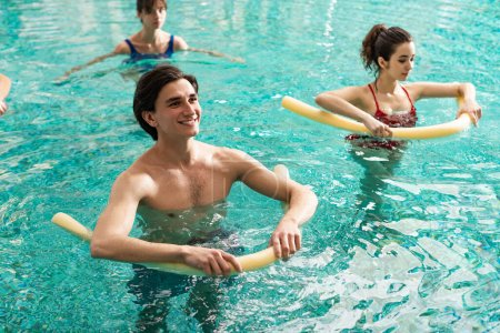 Foto de Selective focus of smiling man holding pool noodles while training with women in swimming pool - Imagen libre de derechos
