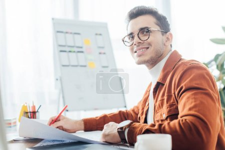 Photo pour Vue latérale du souriant ux designer tenant marqueur tout en travaillant avec des modèles de site Web à la table - image libre de droit