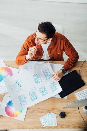 Photo for Overhead view of pensive designer working with templates of user experience design on table - Royalty Free Image