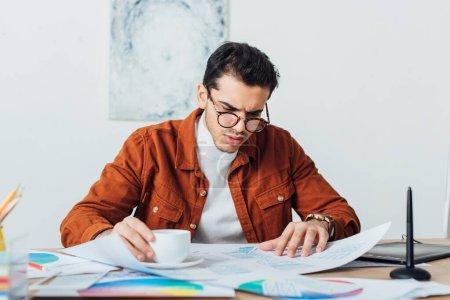 Foto de Diseñador Ux beber café mientras trabaja con plantillas de aplicaciones y círculos de color en la mesa - Imagen libre de derechos