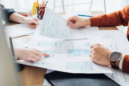 Photo pour Vue recadrée du concepteur travaillant avec des modèles de conception de l'expérience utilisateur du site Web à la table - image libre de droit