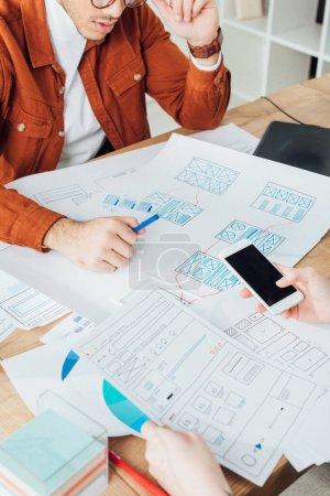 Photo pour Vue recadrée des concepteurs ux à l'aide de smartphones et de cadres d'application de planification pour le site Web mobile à table - image libre de droit