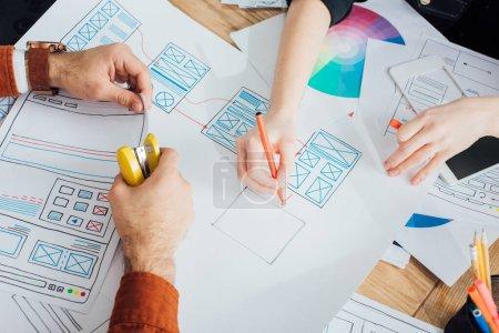 Foto de Cropped view of ux designers with stapler and marker planning app frameworks near smartphone on table - Imagen libre de derechos