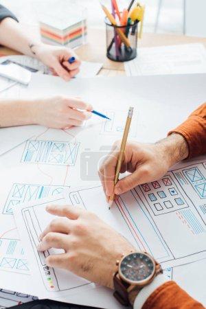 Photo pour Vue agrandie d'un concepteur tenant un crayon pendant qu'il planifie des applications de croquis près d'un collègue à la table - image libre de droit