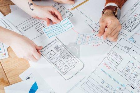 Photo pour Vue agrandie des concepteurs ux planifiant l'interface du site Web mobile avec les mises en page sur la table - image libre de droit