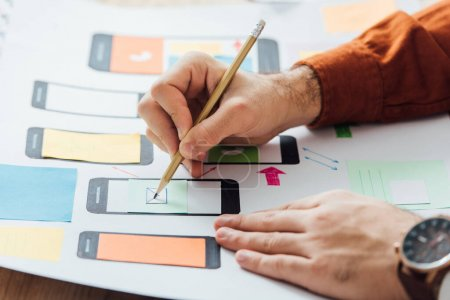 Photo pour Cropped view of developer noticing on app layouts for user experience design of mobile website on table - image libre de droit