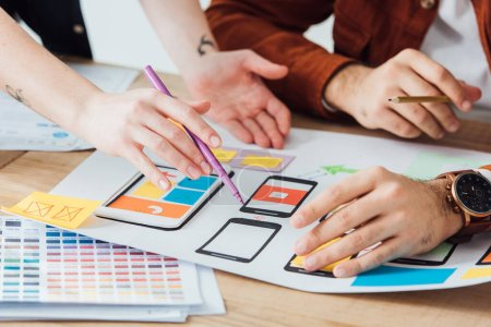 Photo for Cropped view of designers planning user experience design of mobile website with frameworks on table isolated on grey - Royalty Free Image