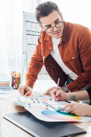 Photo pour Designer regardant collègue avec des mises en page de cadre de la conception de l'expérience utilisateur sur la table - image libre de droit