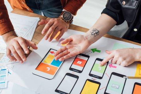 Photo pour Vue recadrée des concepteurs ux travaillant avec des croquis et des mises en page de wireframe mobiles à la table - image libre de droit