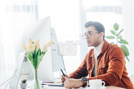 Foto de Vista lateral del diseñador de ux que trabaja con ordenador y tabla gráfica en la mesa en la oficina. - Imagen libre de derechos