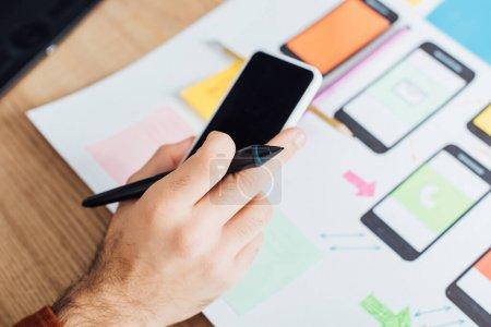 Photo pour Vue recadrée de ux designer à l'aide d'un smartphone et tenant stylet de tablette graphique près des cadres mobiles sur la table isolé sur noir - image libre de droit