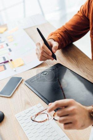 Photo pour Concentration sélective du concepteur ux tenant des lunettes tout en utilisant une tablette graphique près du smartphone et des mises en page sur la table - image libre de droit