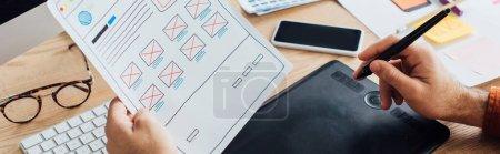 Photo pour Vue recadrée du concepteur en utilisant une tablette graphique tout en planifiant la conception de l'expérience utilisateur du site Web à la table, vue panoramique - image libre de droit