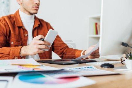Photo pour Vue recadrée du concepteur ux tenant smartphone tout en travaillant avec des esquisses de site Web et palette de couleurs à la table dans le bureau - image libre de droit
