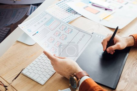 Photo for Cropped view of designer planning ux interface of website and using graphics tablet and laptop on table - Royalty Free Image
