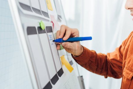 Photo for Cropped view of developer with marker planning ux design of mobile website with templates on whiteboard - Royalty Free Image