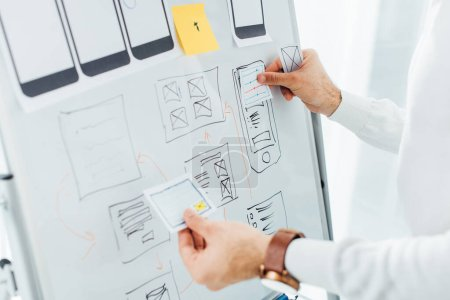 Photo for Cropped view of ux designer using layouts while creative app interface on whiteboard - Royalty Free Image