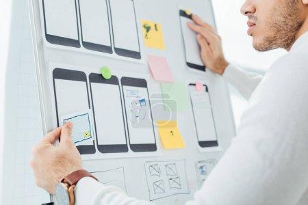 Photo pour Vue recadrée de la conception créative concepteur de site Web mobile avec des modèles sur tableau blanc dans le bureau - image libre de droit