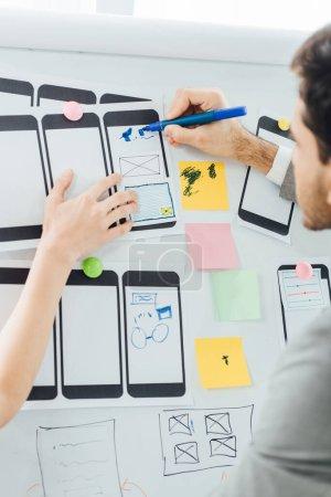 Photo pour Concentration sélective des concepteurs planifiant la conception de l'expérience utilisateur du site Web mobile sur tableau blanc - image libre de droit