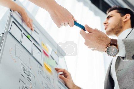 Photo pour Vue à angle bas du concepteur ux donnant marqueur à un collègue près de mises en page sur tableau blanc dans le bureau - image libre de droit