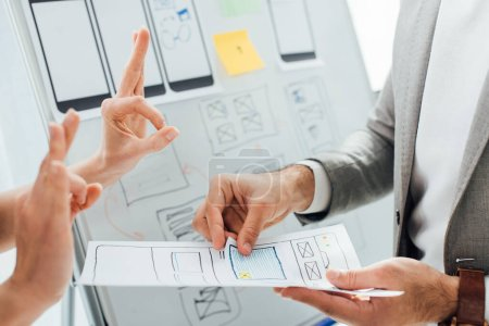Photo for Cropped view of designer showing okay gesture near colleague with layouts of ux design near whiteboard in office - Royalty Free Image