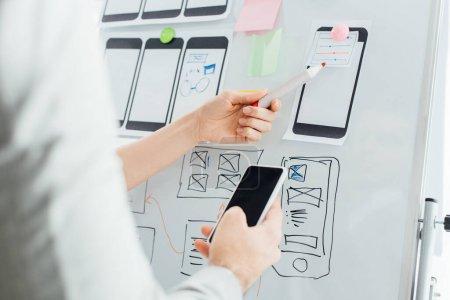 Photo pour Focus sélectif des concepteurs utilisant des mises en page de wireframe sur tableau blanc et smartphone tout en travaillant sur ux design isolé sur blanc - image libre de droit