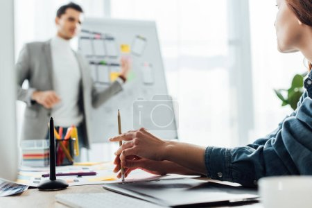 Photo pour Selective focus of ux designer looking at colleague near whiteboard in office - image libre de droit